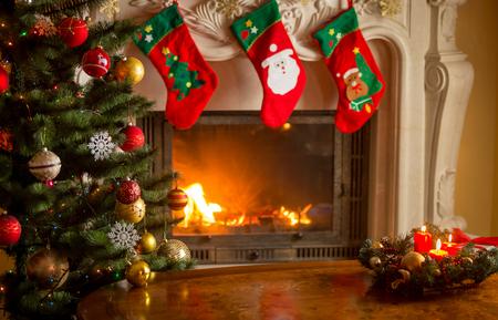 Tavola di legno vuota davanti al camino decorato e albero di Natale. Posto per il testo Archivio Fotografico - 81117292
