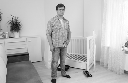 Black and white image of young man posing in bedroom with disassembled furniture