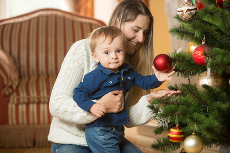 Mother with her 10 months old baby boy decorating Christmas tree at living rom