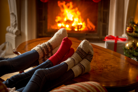 Male and female feet in woolen socks warming at burning fireplace Stockfoto