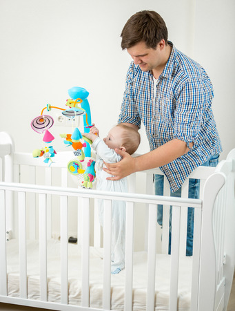 Father holding his 9 months old baby son in cot