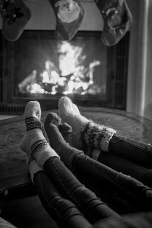 hearthside: Black and white image of family feet in woolen socks warming at fireplace at Christmas eve