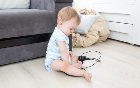 dangerous ideas: Concept of parent irresponsibility. Baby boy sitting alone and playing with electrical cables