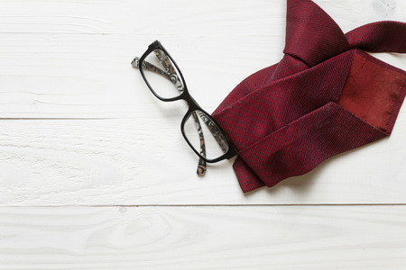 Male necktie and eyeglasses lying on white wooden background