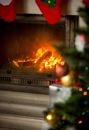 Background of decorated Christmas tree in front of burning fireplace at house