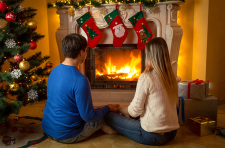 Young couple sitting under Christmas tree and looking at burning fireplace