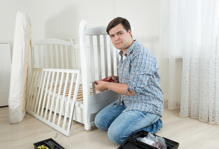 Handyman sitting on floor at empty room and assembling new furniture