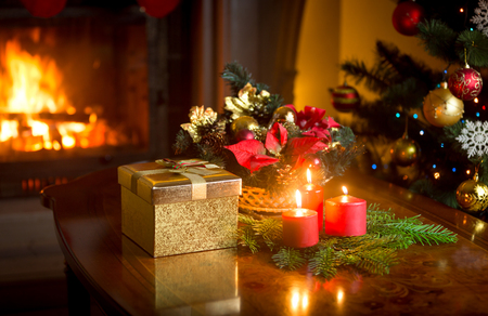 Christmas decorative wreath with burning red candles on table