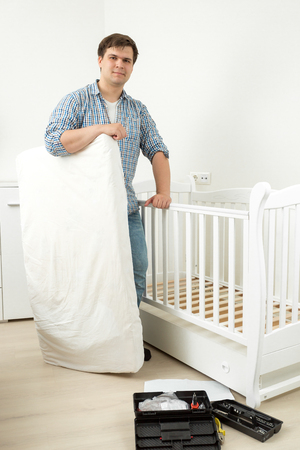 Smiling man standing with mattress at disassembled babys cot Stock Photo