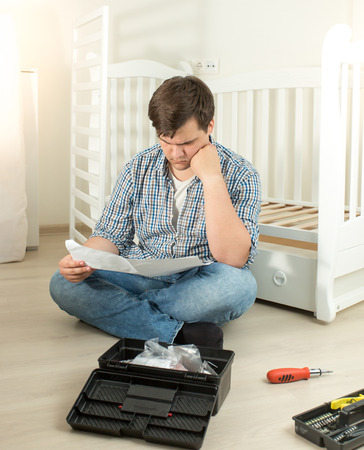 Man confused about assembling furniture reading manual Stock Photo