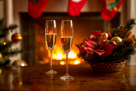 Closeup of two glasses of champagne in front of burning fireplace