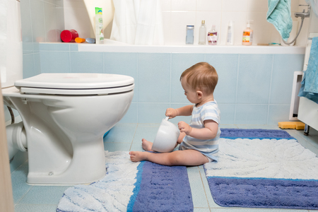 Adorable baby boy sitting on floor at bathroom and playing with toilet paper