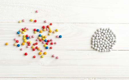 Chaotic colorful balls and organized white balls. Conceptual image of order and chaos