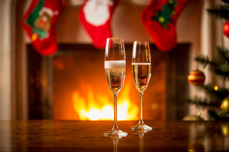 Two glasses being filled with champagne on Christmas table in front of fireplace