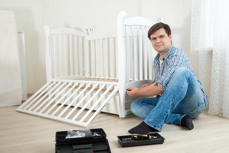 Handyman assembling wooden furniture in childrens room