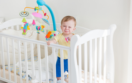 Upset baby boy crying and holding to the side of crib