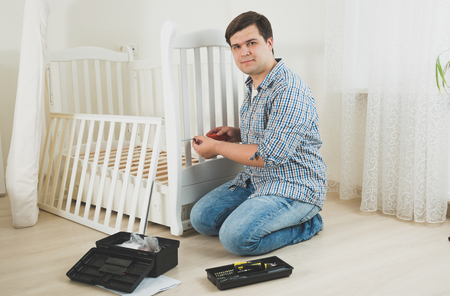 Young man disassembling furniture in nursery Stock Photo