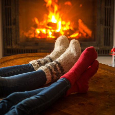 Family wearing socks sitting in chalet by burning fireplace Stock Photo