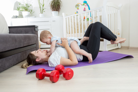 Happy mother doing exercise at home and having fun with her baby boy