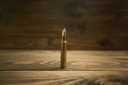 Closeup image of riffle bullet on old wooden desk
