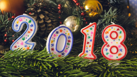 Closeup toned image of 2018 New Year candles on Christmas wreath