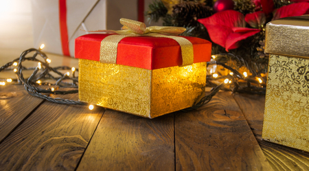 closeup image of red christmas gift box with golden ribbon and glowing lights stock photo