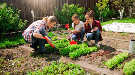 Happy young woman with daughters planting seeds in garden Stockfoto
