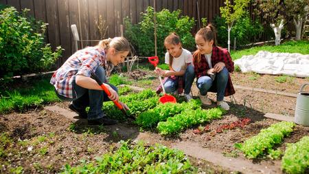 Gelukkige jonge vrouw met dochters die zaden in tuin planten Stockfoto