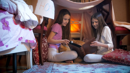 Two cute girls in pajamas sitting in selfmade tent in bedroom and reading big book