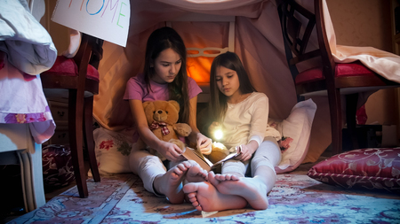 Two girls wearing pajamas with flashlight and book in selfmade tent at bedroom