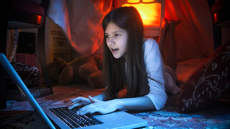 Portrait of teenage girl lying on floor in bedroom at night and using laptop