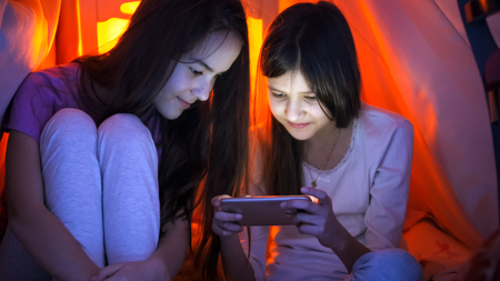 Portrait of two teenage girls in pajamas browsing internet on mobile phone at night Stock Photo