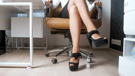 Sexy woman wearing high heels shoes and short skirt sitting in office chair
