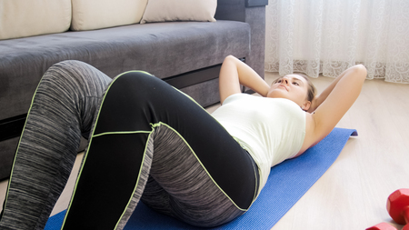 Beautiful young woman in leggings doing sit ups at home