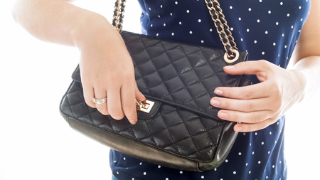 Closeup photo of young woman locking her black leather handbag Фото со стока