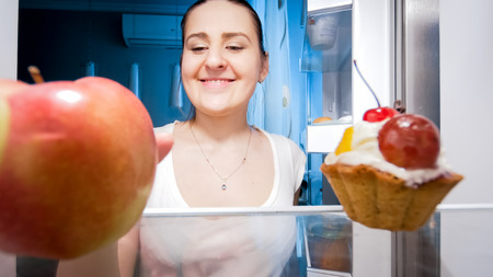 Portrait of young smiling woman taking apple from refrigerator at night Stock Photo