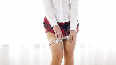 Closeup photo of sexy woman in schoolgirl uniform taking off panties 免版税图像