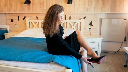 Elegant young woman in black dress sitting on bed at hotel room and taking off shoes Banque d'images
