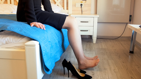 Closeup photo of young elegant barefoot woman sitting on bed and stretching legs Banque d'images