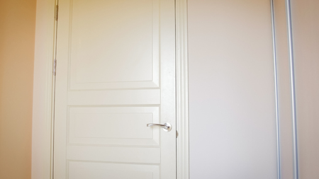 Closeup photo of white wooden door at hotel room