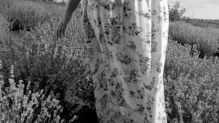 Black adn white closeup image of young woman in dress walking at lavender field