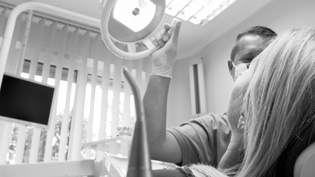 Black and white closeup image of dentist adjusting lamp Stock Photo