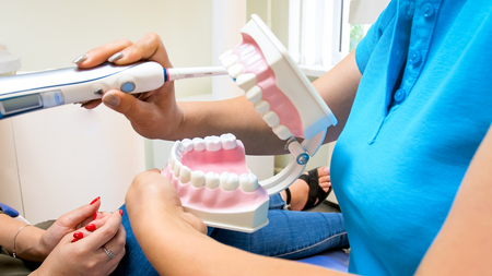 Closeup image of dentist showing how to take care of teeth with electric toothbrush