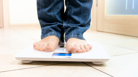 Young barefoot woman in jeans standing on digital scales
