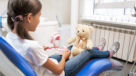 Cute girl pretending as her teddy bear is patient in dentist office