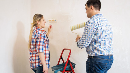 Young couple painting walls at home with paint rollers