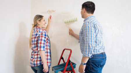 Smiling young couple painting walls in new house