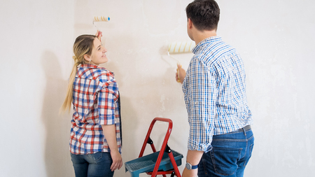 Smiling young woman painting walls with her husband in new home