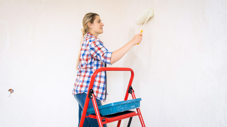 Beautiful smiling young woman with paint roller doing renovation at home
