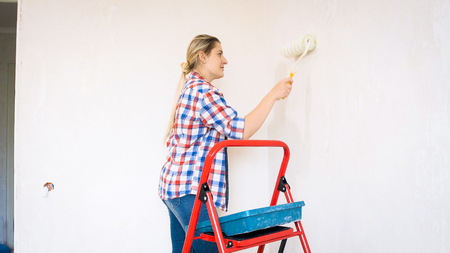 Beautiful young woman in checkered shirt painting walls with paint roller Stock Photo